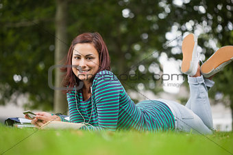 Smiling casual student lying on grass looking at camera