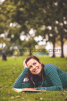 Smiling casual student lying on grass looking up