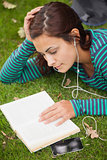 Calm casual student lying on grass reading a book