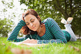 Smiling casual student lying on grass reading a book