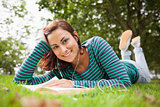 Cheerful casual student lying on grass reading a book