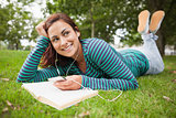 Smiling casual student lying on grass listening to music