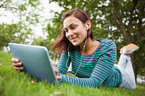 Smiling casual student lying on grass using tablet