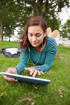 Calm casual student lying on grass using tablet