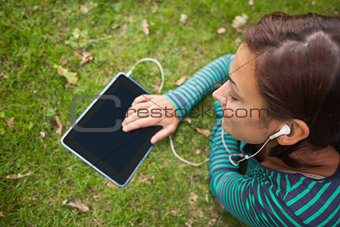 Casual student lying on grass using tablet