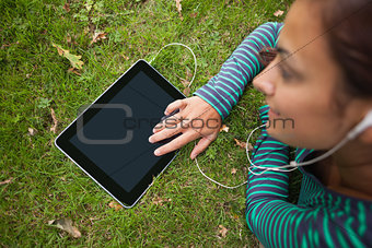 Casual student lying on grass using tablet listening to music