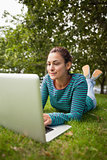 Casual student lying on grass using laptop