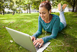 Smiling casual student lying on grass using laptop