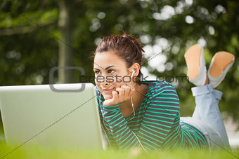 Thoughtful casual student lying on grass using laptop