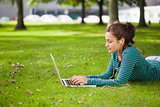 Calm casual student lying on grass using laptop
