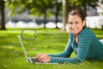 Attractive casual student lying on grass using laptop looking at camera