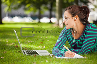 Attractive casual student lying on grass taking notes