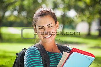 Casual cheerful student holding books