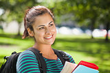 Casual smiling student holding books