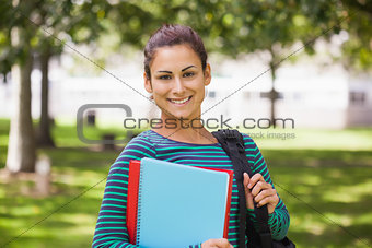 Casual cheerful student looking at camera holding books