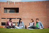 Four casual students sitting on the grass chatting