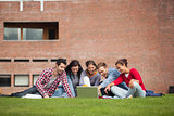 Five casual students sitting on the grass pointing at laptop