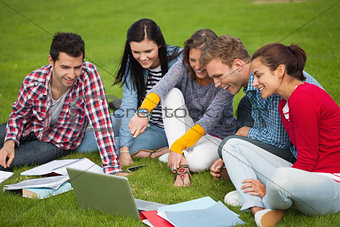 Five students sitting on the grass pointing at laptop