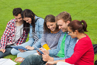 Five students sitting on the grass using tablet