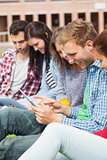 Five casual students sitting on the grass using tablet