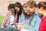 Five smiling students sitting on the grass using tablet