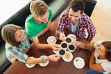 Four happy students having a cup of coffee chatting