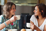 Two smiling students having a cup of coffee