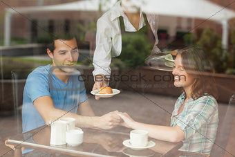 A couple holding hands while waitress serving food