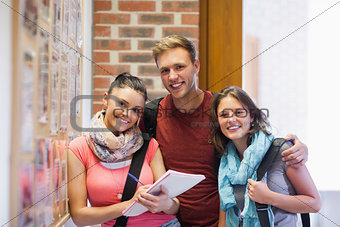 Three smiling students standing next to notice board