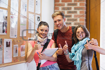 Three smiling students standing next to notice board showing thumbs up
