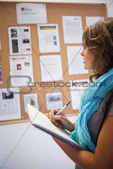 Casual student taking notes in front of notice board