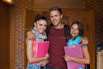 Three smiling students posing in hallway