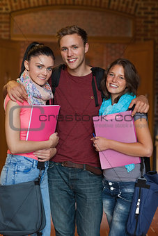 Three cheerful students posing in hallway