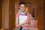 Pretty smiling student standing in hallway