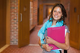 Cute smiling student standing in hallway
