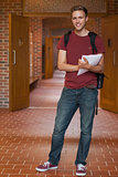 Handsome cheerful student standing in hallway