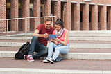 Happy students sitting on stairs using tablet