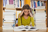 Frustrated pretty student studying between piles of books