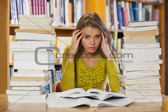 Tired pretty student studying between piles of books