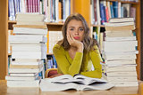 Exhausted pretty student studying between piles of books