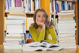 Thoughtful pretty student studying between piles of books