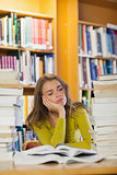 Exhausted beautiful student studying between piles of books