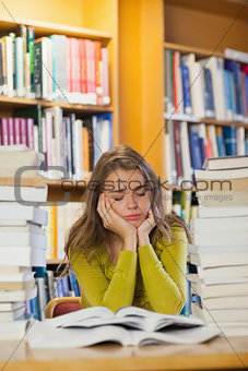 Tired beautiful student studying between piles of books with closed eyes