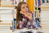 Serious pretty student sitting between piles of books