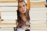 Stern pretty student studying between piles of books