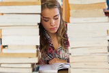 Concentrated pretty student studying between piles of books