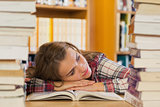 Tired pretty student resting head on table between piles of books