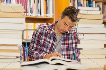 Focused handsome student studying between piles of books