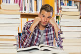 Irritated handsome student studying between piles of books