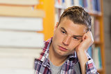 Exhausted handsome student studying between piles of books